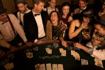 Group of people at a poker table, drinking and laughing.