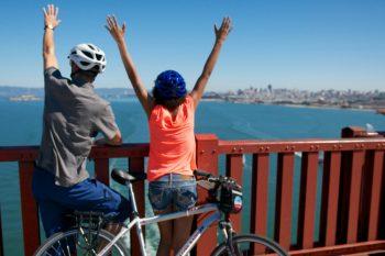 People enjoying the view while biking across the Golden Gate Bridge.